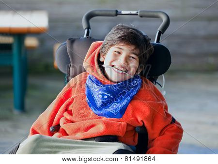 Handsome, Happy Biracial Eight Year Old Boy Smiling In Wheelchair Outdoors