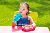 Toddler kid girl drinking eating macaroni pasta in garden turf grass outdoor poster