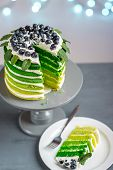 Cuted piece of green sponge cake on the plate on festive background with bokeh light poster