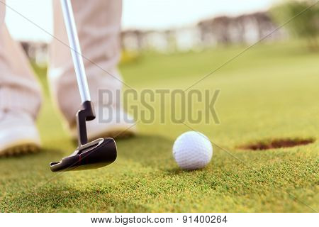 Close up of man putting ball into hole