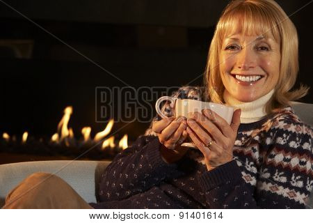 Mature woman relaxing in front of fire at home