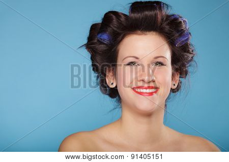 Girl preparing to party. Headshot of young woman with hair curlers pin up makeup studio shot on blue poster