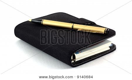 The Closed Pad And The Pen On A White Background
