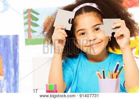 Portrait of African girl holding puzzle pieces
