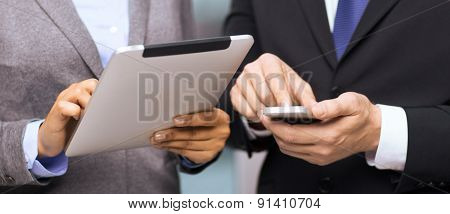 business, technology, internet and office concept - businessman and businesswoman with smartphone and tablet pc computer in office