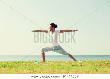 fitness, sport, people and lifestyle concept - smiling man making yoga exercises outdoors