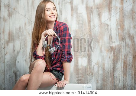 Cheerful hipster woman is holding her headphones