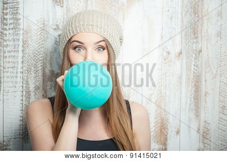 Pretty hipster woman is inflating colored balloon