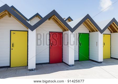 Colourful Doors Of Yellow, Green And Red, With Each One Being Numbered Individually, Of White Beach