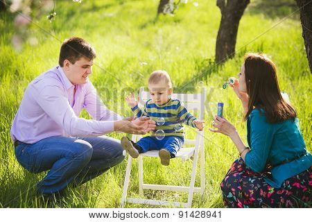 father and mother blowing soap bubbles. family playing outside