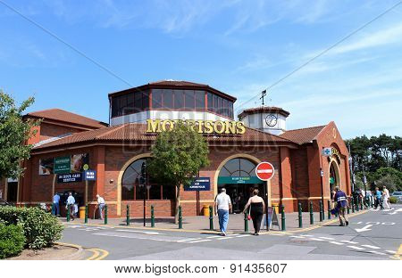 SCARBOROUGH, NORTH YORKSHIRE, ENGLAND - 15th of July 2013: People walking into the Morrisons supermarket to do their weekly shopping. This is one of the most popular supermarkets in England.