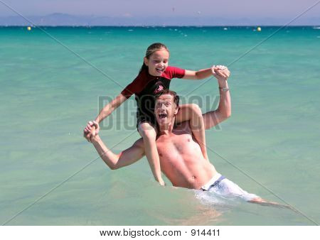 Young Father And Daughter Playing On Beach In Sea