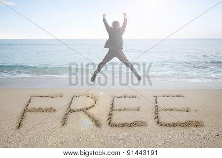 Jumping Businessman Cheering With Free Word Handwritten In Sand Beach