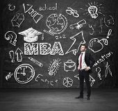 Senior manager is going to get the master's degree in business administration. A concept of the MBA degree. Drawn educational icons on the chalkboard. poster