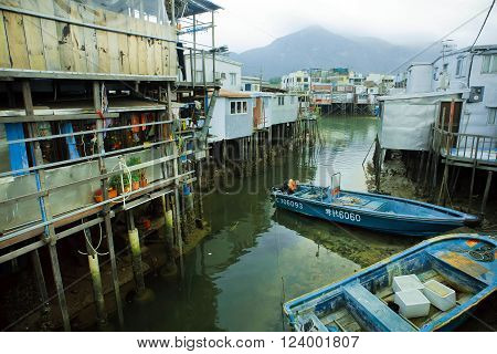 HONG KONG, CHINA - FEB 11: Riverboats of fishermen near metal houses on wooden stilts in poor village on February 11, 2016. Hong Kong dollar is the eighth most traded currency in the world.