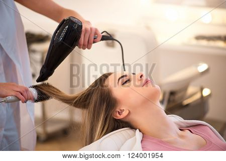Women paradise  Delighted beautiful woman sitting in the hairdressing salon while professional hairdresser holding hairdryer and drying her hair poster