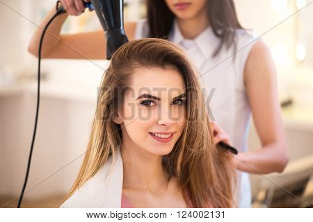 Breath of beauty. Cheerful charming woman sitting in the hairdressing salon and smiling while professional hairdresser drying her hair