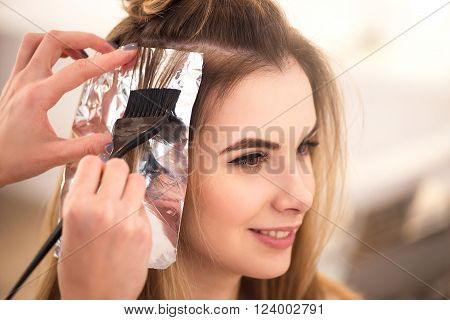 Make it properly. Beautiful charming woman sitting in the hairdressing salon while professional hairdresser dyeing her hair