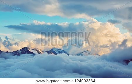 alpine landscape with peaks covered by snow and clouds. natural mountain background