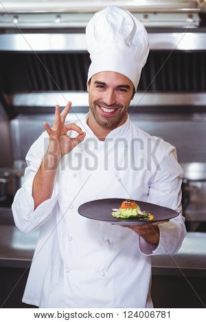 Male chef holding plate and doing ok sign in commercial kitchen