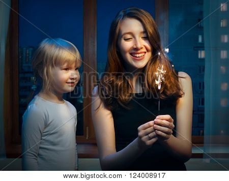 An adult woman and a little girl at the window with a sparkler. Girls sister. Outside, the night city. She laughs merrily. The kid looks at the fire sparks