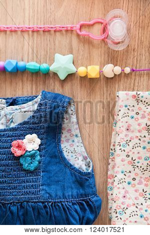 Close up top view of jeans girl's dress decorated with red blue white flovers beige girl's panties with blue brown red flovers pattern and colored silicone beads and pink nipple with pink nipple holder on wooden background