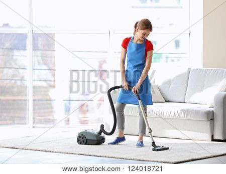 Cleaning concept. Young woman cleaning carpet with vacuum cleaner