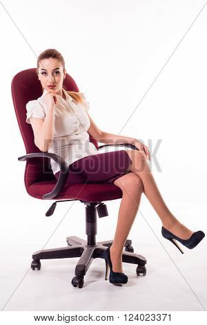 Cute office girl sitting on red chair and look to camera with serios face