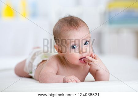 lying baby child wearing nappy at home
