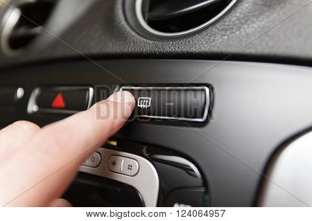 Man pressing button defrost in the car (Shallow DOF).