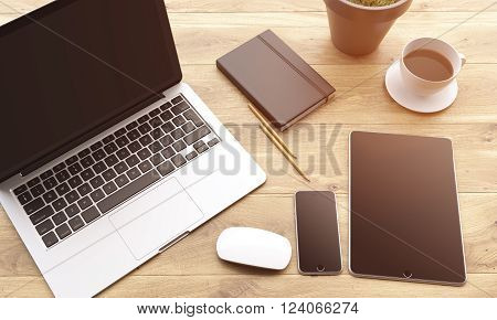 Laptop smartphone and tablet with black screens coffee plant pencils and datebook on wooden table. Concept of workplace. Mock up. 3D rendering