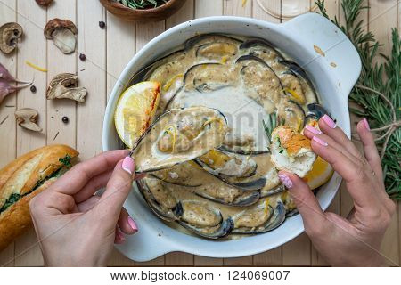 Woomen hold baked mussel in creamy sauce, top view