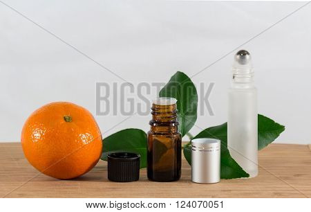 Orange Essential Oil Bottle and Roller with Citrus Leaves.