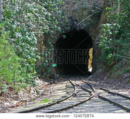 merging railroad tracks go through a small tunnel