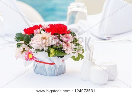 Close up chrysanthemum and carnation flower bouquet and polyscias leaf decoration on dining table