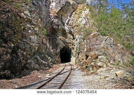 railroad tracks curve into a tunnel carved in sandstone