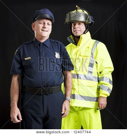 Police officer and firefighter photographed together over a black background.