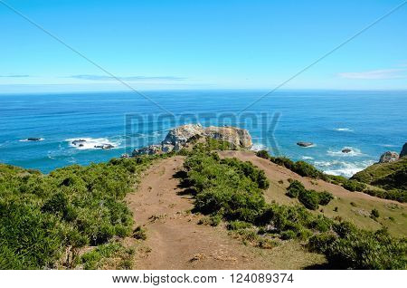 Coastal view onto the Muelle de las Almas with a clear blue sky and green hills poster