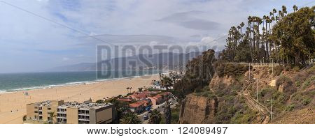 Along the Santa Monica coastline with a blue sky over the white sand of the beach in Southern California.