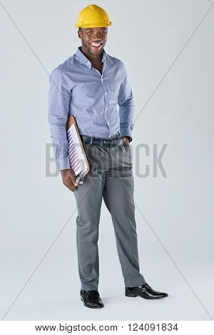 Full length portrait of black african business man architect construction manager in formal attire and yellow hardhat, isolated in studio