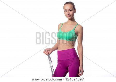 Fitness woman in sports style with a measuring tape standing on a white background