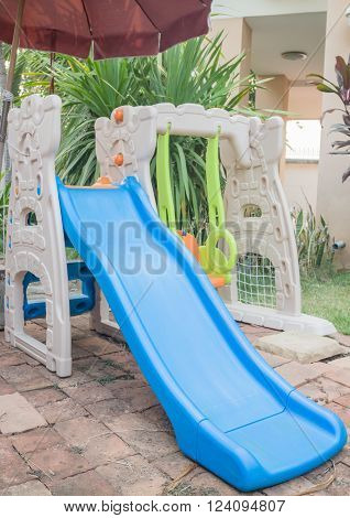 Home playground swing set in garden, stock photo
