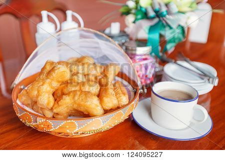 Chinese traditional snacks deep fried dough stick (Pa Tong Go) in basket with hot coffee on wood table. Chinese Food. Thai food.