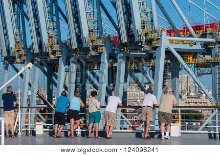 Montevideo Uruguay - December 15 2012: Passengers aboard a cruise ship standing on the deck and looking to a large Container Terminal in the Montevideo industrial harbor.