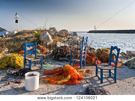 Multicolored fishing nets blue chairs on the pier and small lighthouses next to the sea Skopelos island; Sporades; Greece