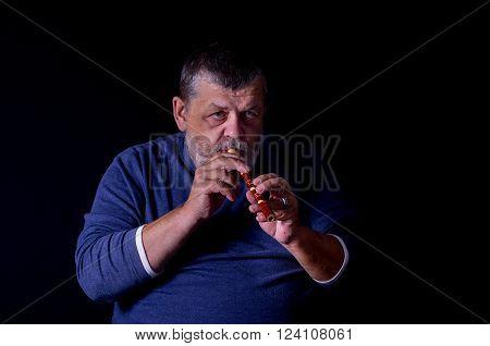 Portrait of old musician playing Ukrainian woodwind instrument sopilka