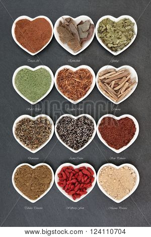 Herb selection for mens health used in natural alternative herbal medicine in heart shaped white porcelain dishes over slate background with titles.