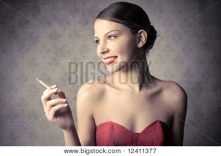 Smiling beautiful woman holding a cigarette