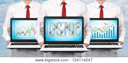 Three businessman standing in office and holding laptop with business development concept on screen