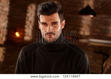 Portrait of handsome bristly man, looking at camera in black turtleneck.